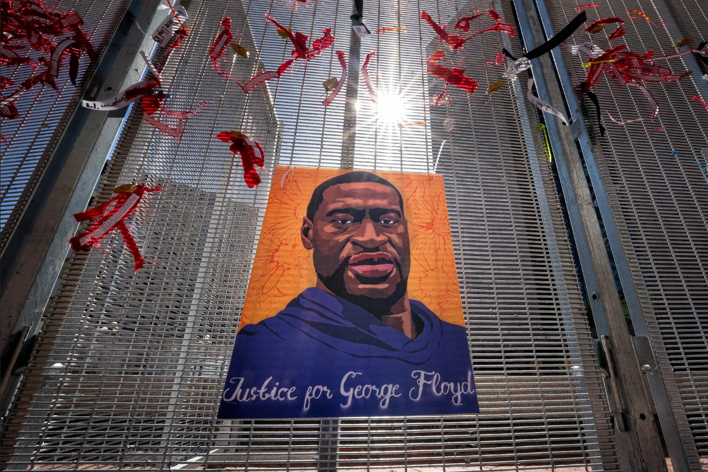 """""""Justice for George Floyd"""" in script lettering on a portrait of George Floyd mounted on a tall steel fence. With red fluttering decorations hovering around him."""
